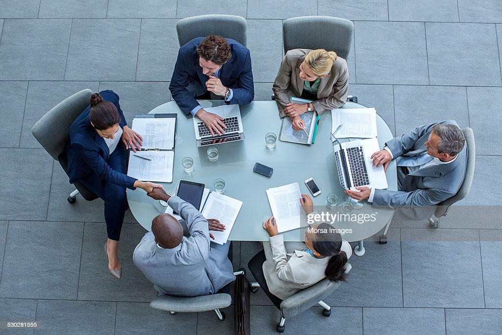 Businesspeople shaking hands at conference table : Stock Photo