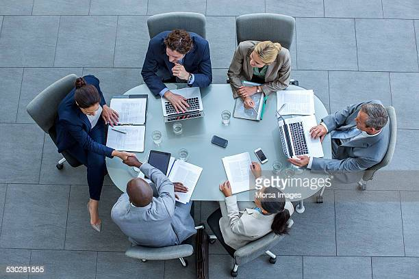 businesspeople shaking hands at conference table - tavolo da conferenza foto e immagini stock