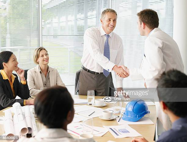 Businesspeople shaking hands in conference room