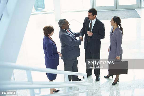 Businesspeople Shaking Hands in Lobby