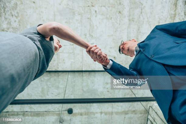 businesspeople shaking hands - unusual angle stock pictures, royalty-free photos & images