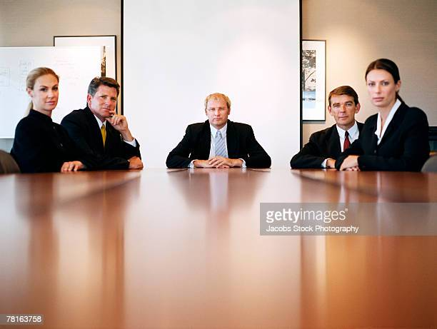 businesspeople sitting at a boardroom table - conselho diretor - fotografias e filmes do acervo