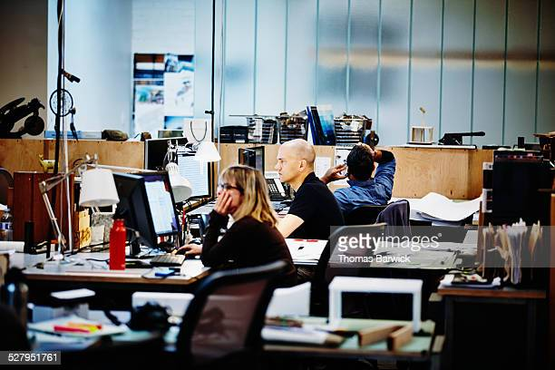 businesspeople sitting at workstations in office - leanintogether stock pictures, royalty-free photos & images