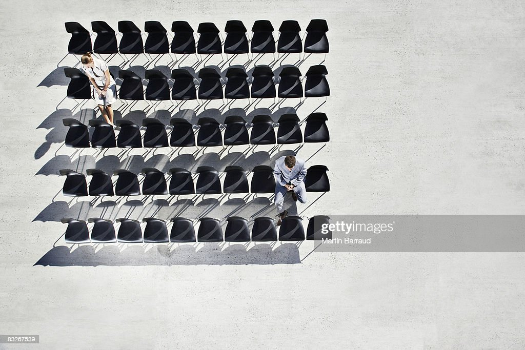 Businesspeople sitting in office chairs on sidewalk : Stock Photo