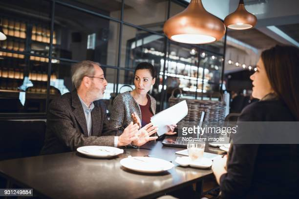 Businesspeople sitting in restaurant and having meeting