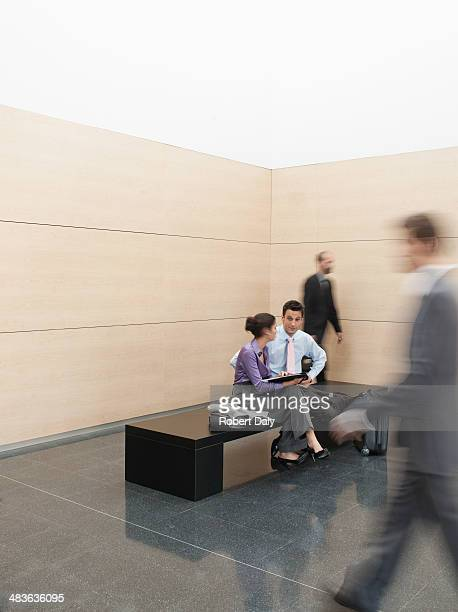 businesspeople sitting on bench in lobby - lingering stock pictures, royalty-free photos & images