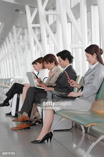 Businesspeople sitting on bench, using cellular phones and PC