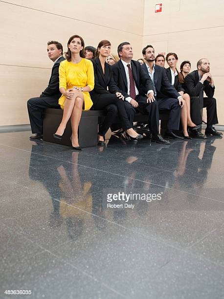 businesspeople sitting on crowded bench - different cultures stock pictures, royalty-free photos & images