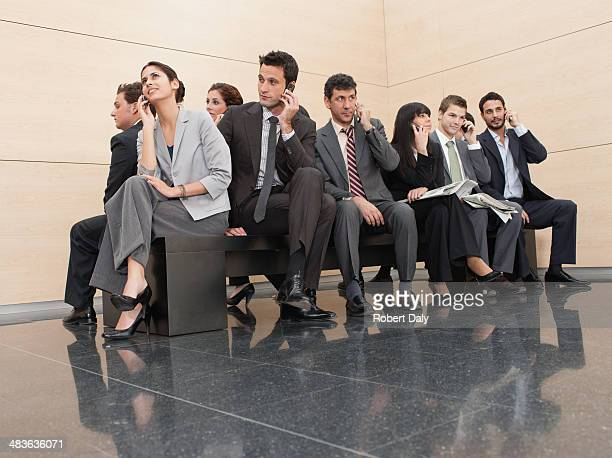 businesspeople sitting on crowded bench - lingering stock pictures, royalty-free photos & images