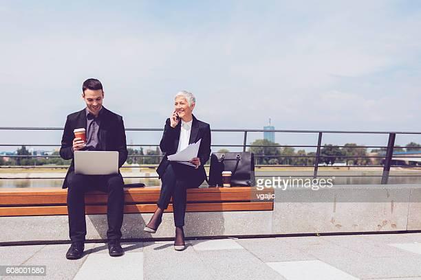 Geschäftsleute sitzen auf der Bank und mit Digitaltablett.