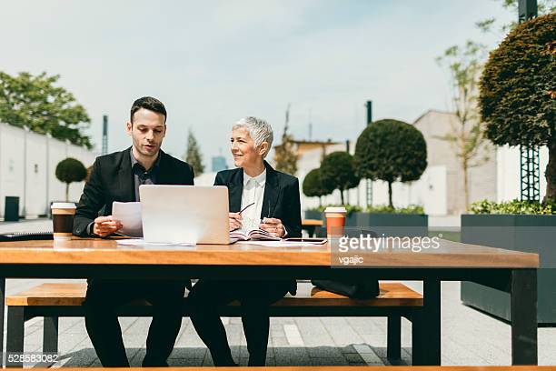 Businesspeople Sitting Outdoors And Using Laptop.