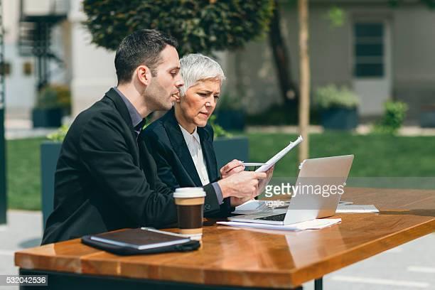 Uomini d'affari seduto all'aperto In Tech Parco e usando il Computer portatile.