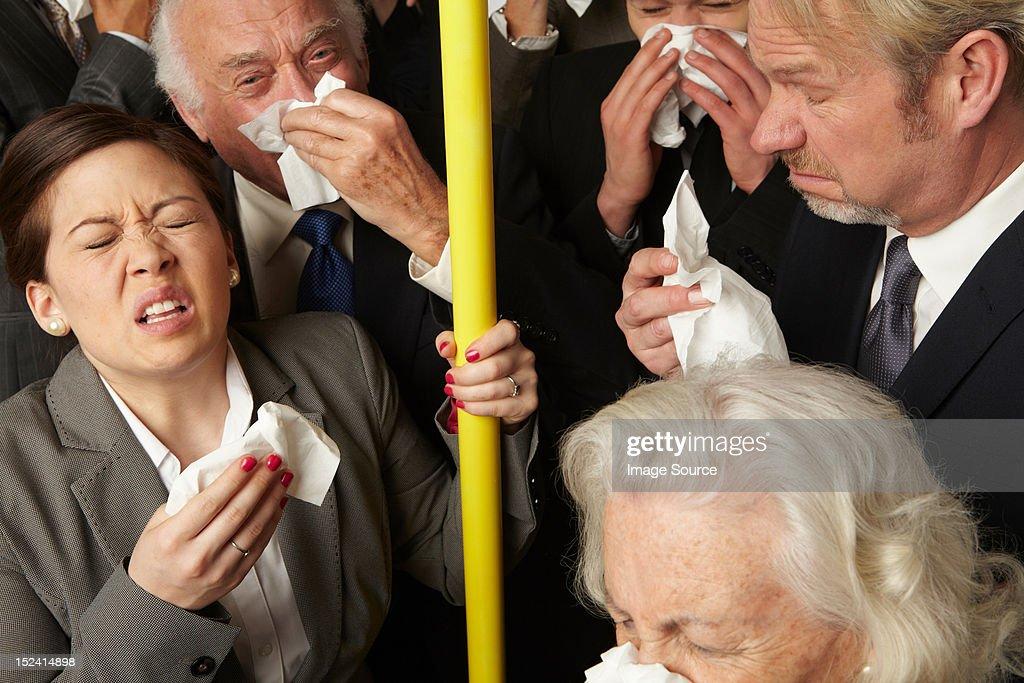 Businesspeople sneezing on subway train : Stock Photo