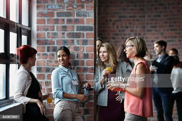 businesspeople socializing by window of auditorium - 人脈作り ストックフォトと画像