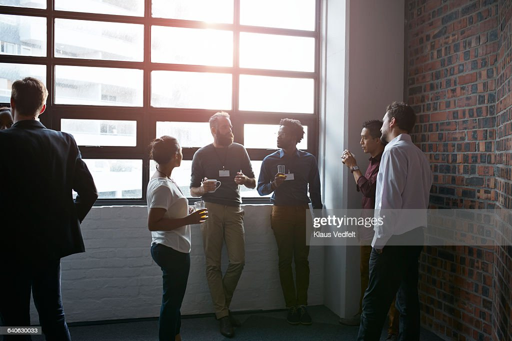 Businesspeople socializing by window of auditorium : Stock Photo