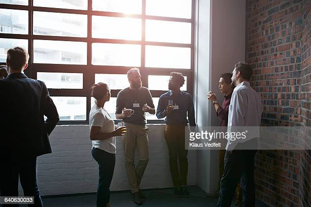 businesspeople socializing by window of auditorium - fare una pausa foto e immagini stock