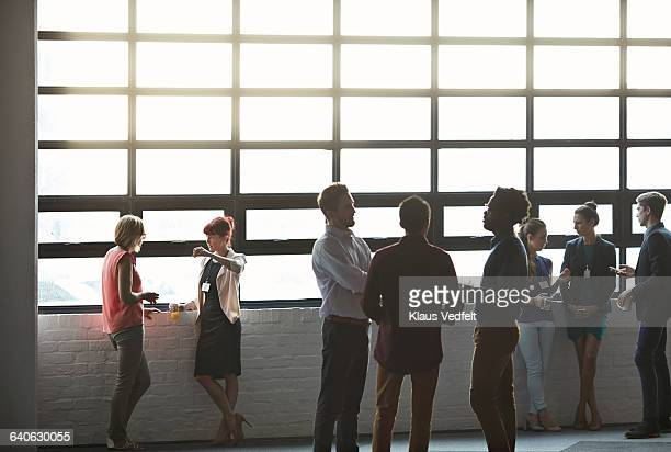 Businesspeople socializing by window of auditorium