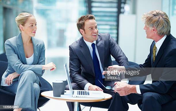Businesspeople speaking around a laptop