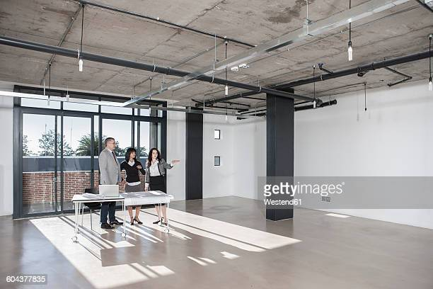 Businesspeople standing and talking in new open office