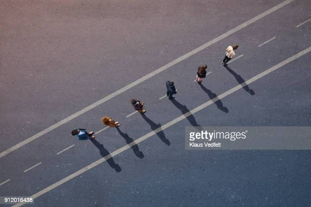 Businesspeople standing in line across road painted on asphalt