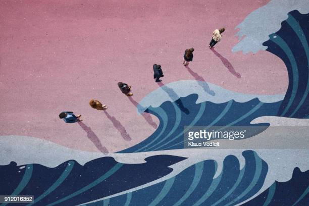 Businesspeople standing in line with big panted waves on asphalt