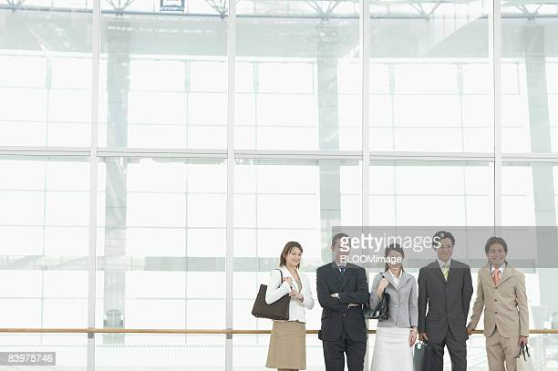 Businesspeople standing in row, smiling