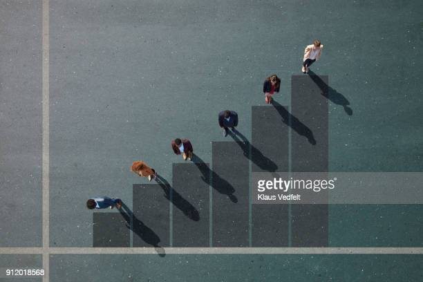 Businesspeople standing on painted bar chart on asphalt