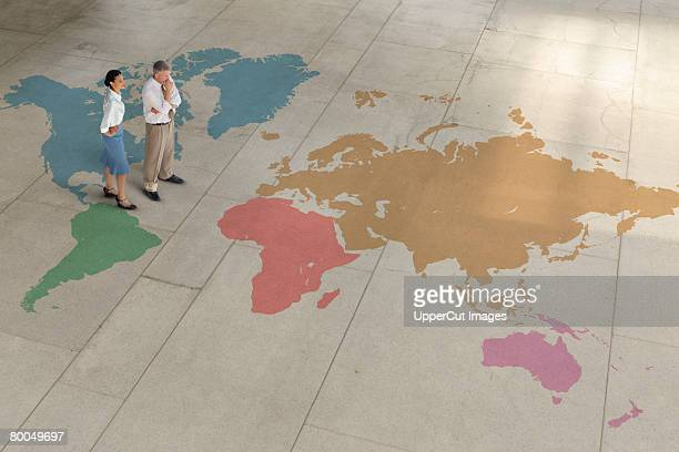 Businesspeople standing on world map
