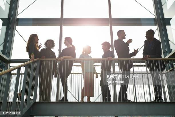 businesspeople standing & talking on staircase at sunset - 人脈作り ストックフォトと画像