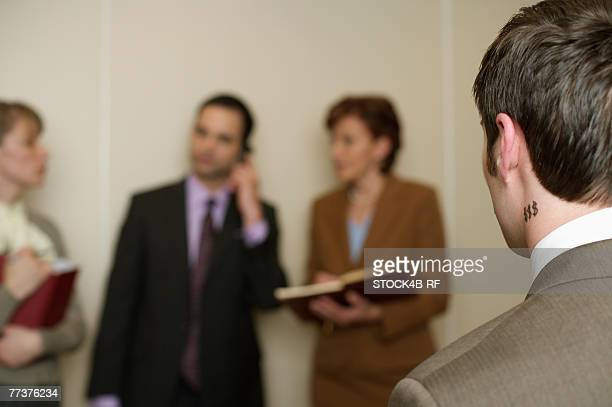 Businesspeople standing together, businessman with dollar sign tattoo in foreground
