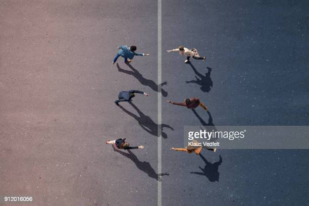 Businesspeople stretching towards each other, on painted asphalt