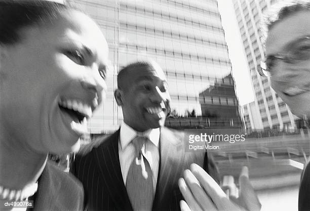 Businesspeople Talking and Laughing Outside of Office Building