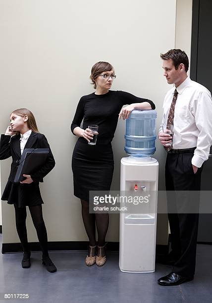 Businesspeople talking by the water cooler