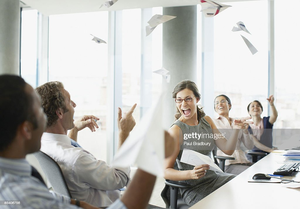 Businesspeople throwing paper airplanes in office : Stock Photo