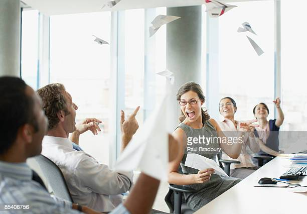 businesspeople throwing paper airplanes in office - wasting time stock pictures, royalty-free photos & images