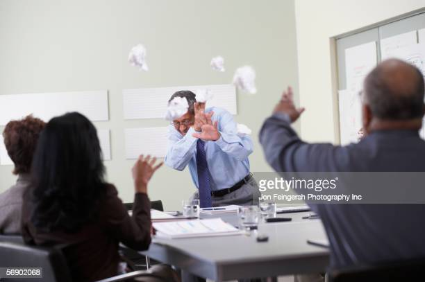 businesspeople throwing paper balls - negative emotion stock pictures, royalty-free photos & images