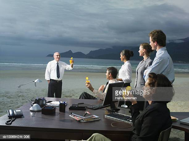 Businesspeople toasting drinks on beach