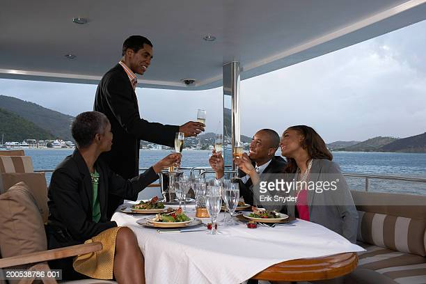 Businesspeople toasting each other over meal on yacht