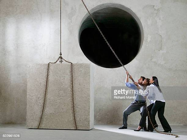 Businesspeople Trying to Lift Cube Into Round Hole with Pulley