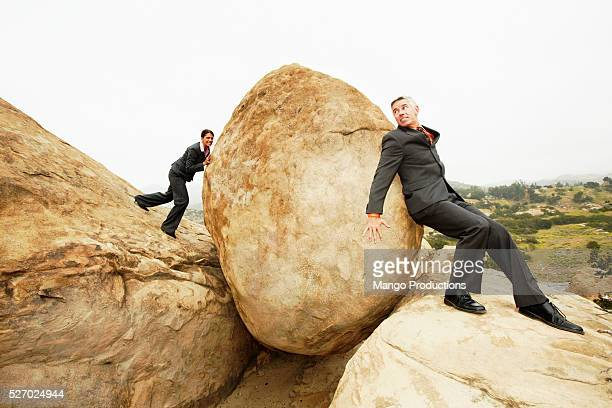 Businesspeople Trying to Push Boulder
