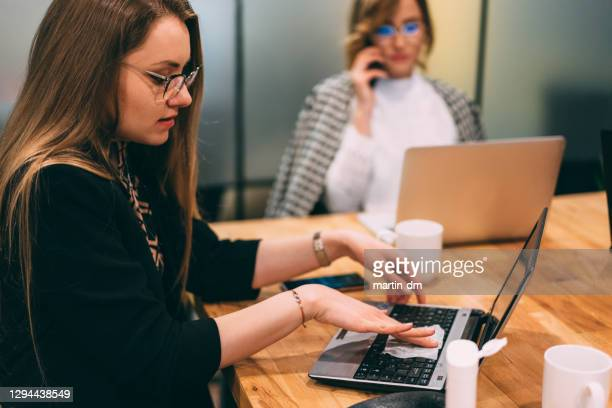 businesspeople using antiseptic wipes at work - antiseptic wipe stock pictures, royalty-free photos & images