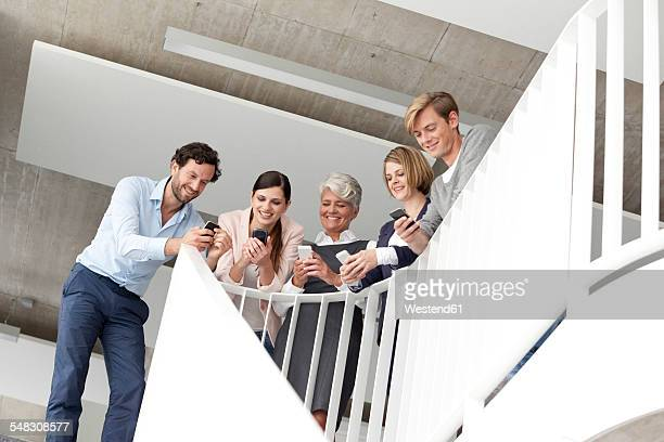 Businesspeople using cell phones in staircase
