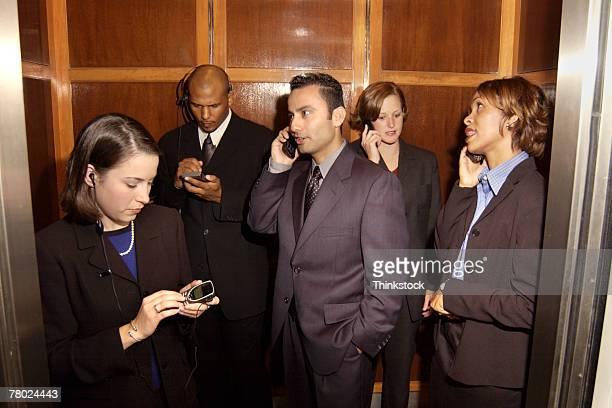 Businesspeople using cellular phones in elevator