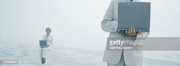 businesspeople using laptops on beach - hot desking stock pictures, royalty-free photos & images