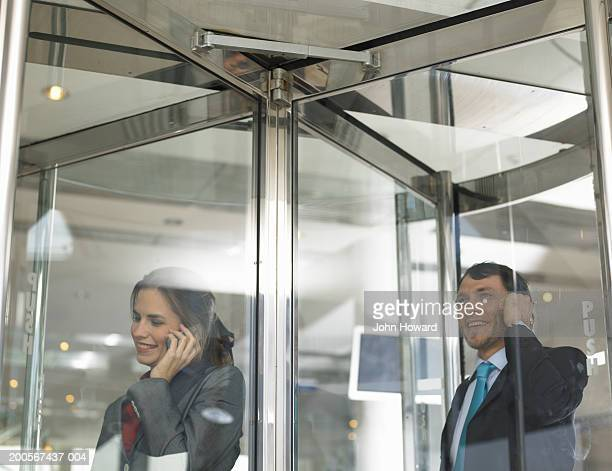 Businesspeople using mobile phone in revolving door