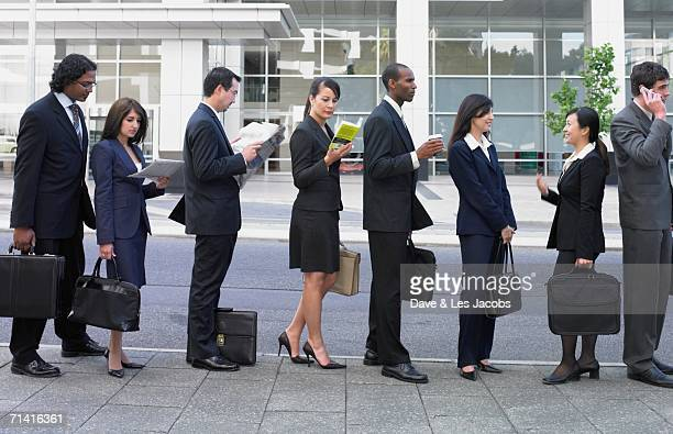 Businesspeople waiting on line outdoors