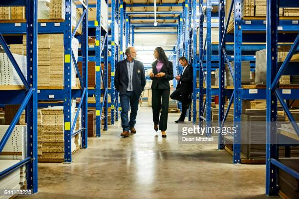 Businesspeople waking through warehouse