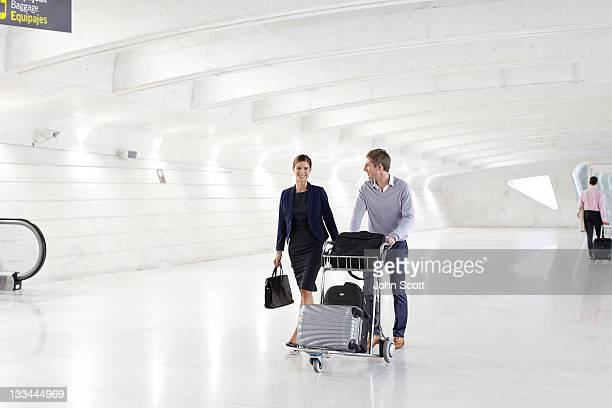 Businesspeople walk through airport with luggage