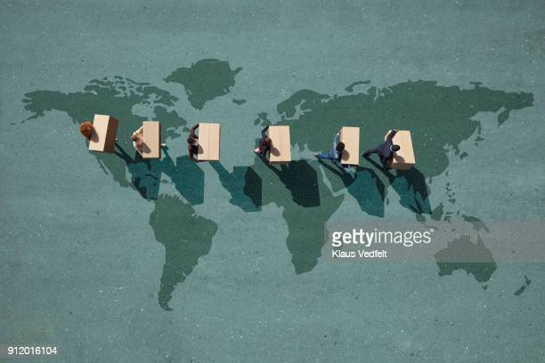 Businesspeople walking across painted world map, carrying moving boxes