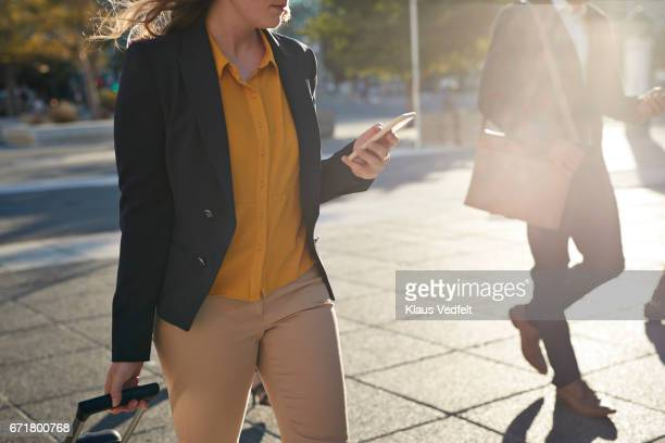 Businesspeople walking across square looking at phones